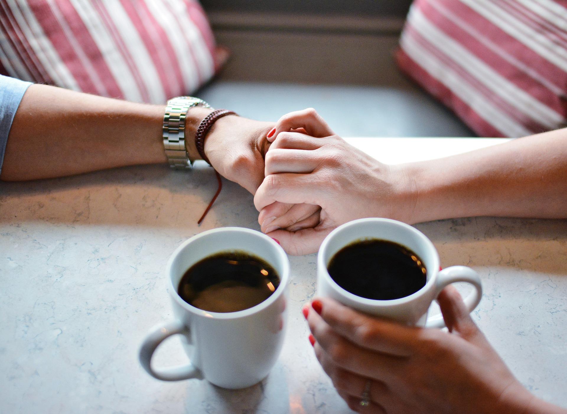 コーヒーとともに手を握る男女