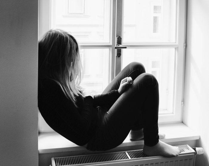 窓辺にもたれる女性