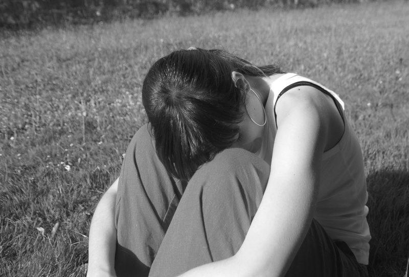 膝に顔をうずめる女性