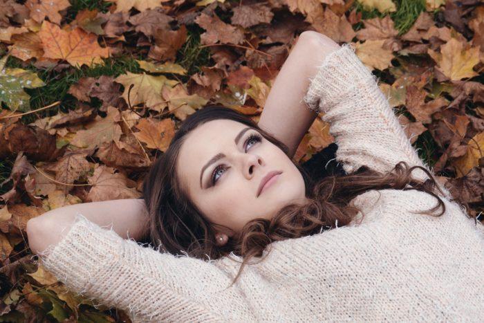 落ち葉の上に寝ころぶ女性