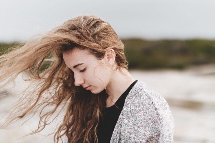 髪をなびかせうつむく女性