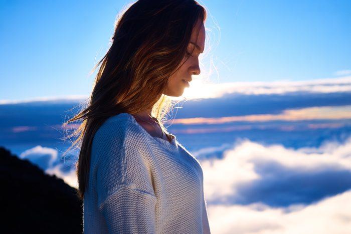 空と雲をバックにうつむく女性