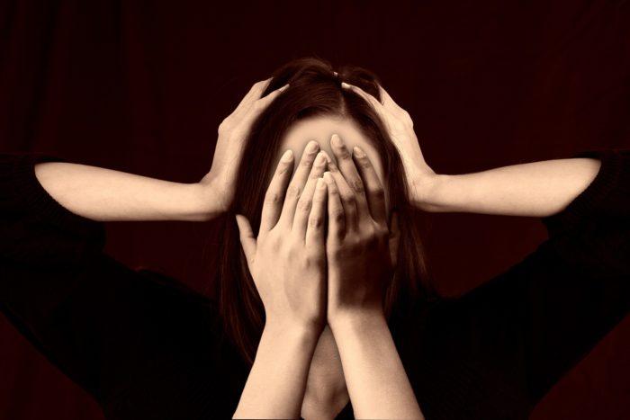 頭と顔を押さえる女性