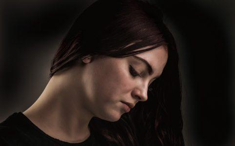 黒髪うつむく女性