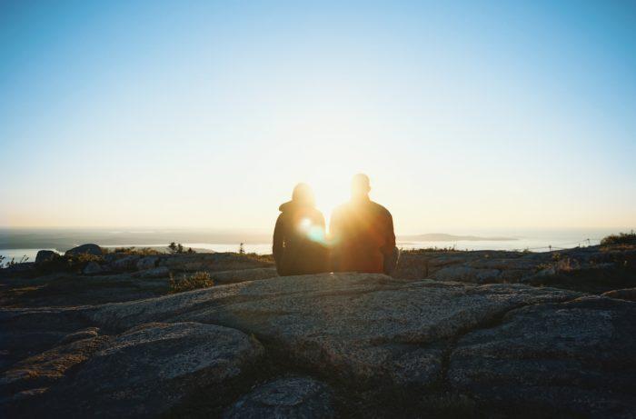 朝日に向かって座るカップル
