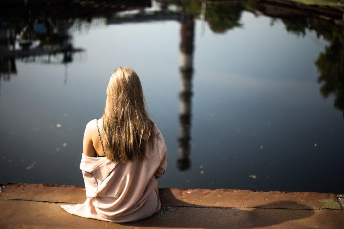 水辺に座るブロンド女性