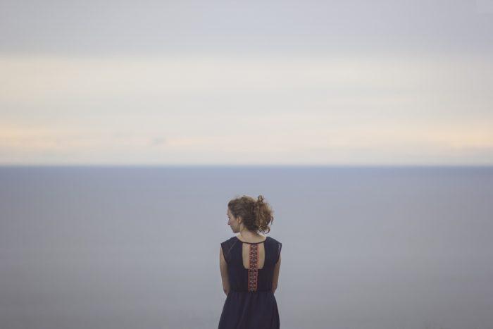 海をバックに後ろ姿の女性