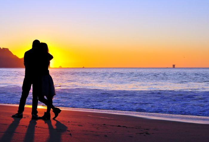 サンセットビーチでハグする男女