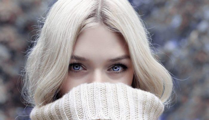 セーター口を隠す女性