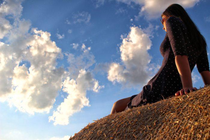 青空の下座る女性