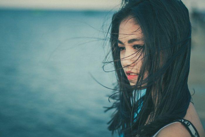 水辺で髪をなびかせる女性
