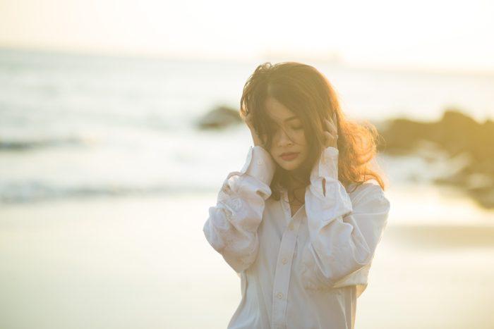 海辺で両手で耳を抑える