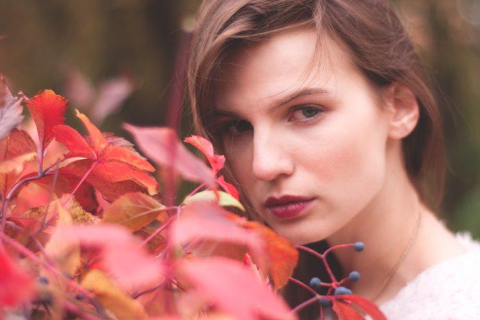 赤い花の横の女性
