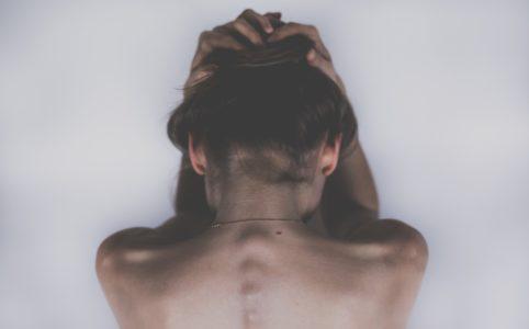 頭を抱える後ろ姿の女性