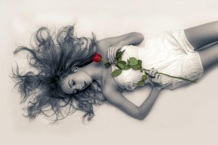 バラを持ち横たわる女